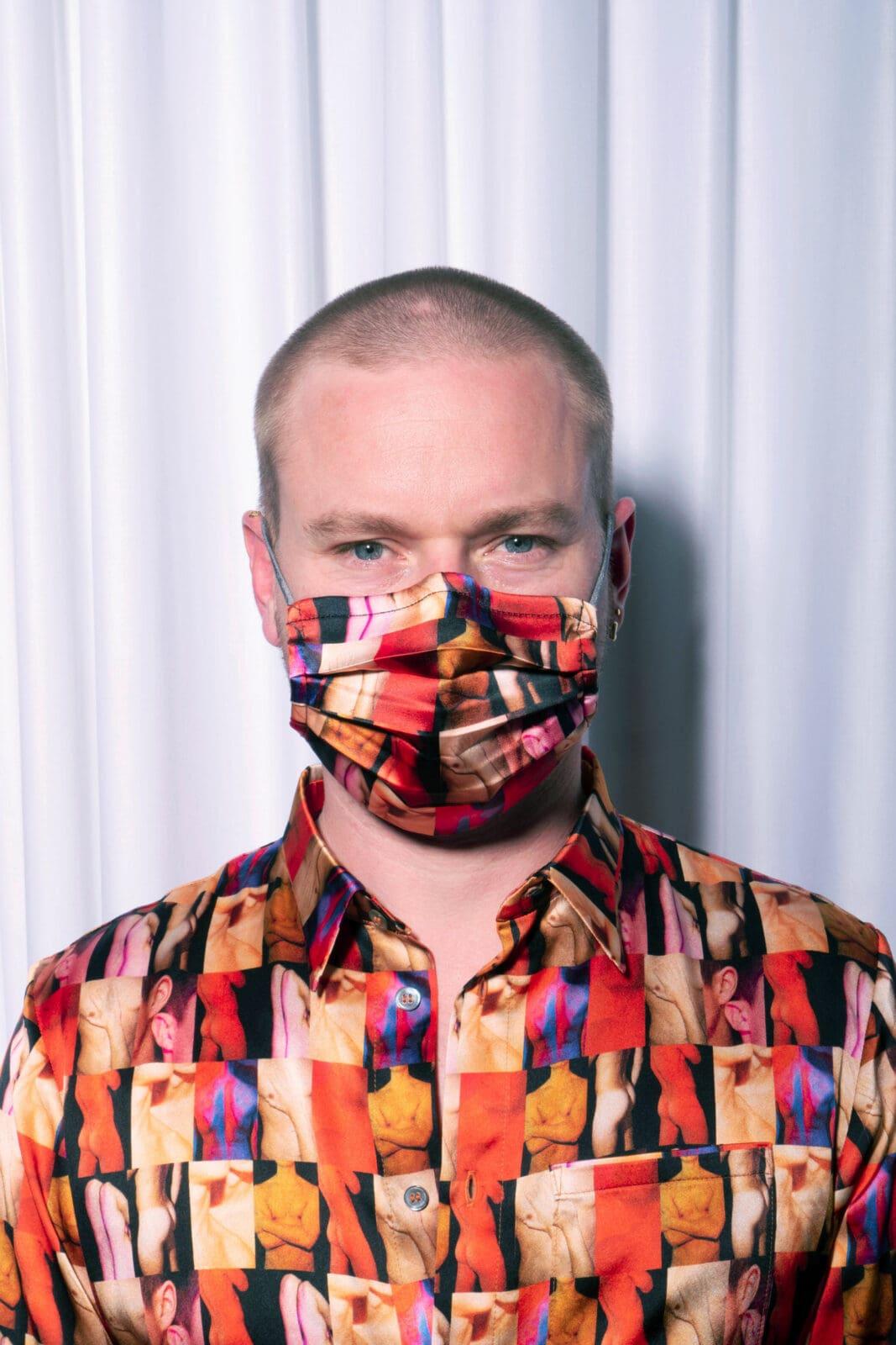 Mann mit uniformer Schutzmaske und Hemd posiert für Produkteshooting für Schutz-Masken