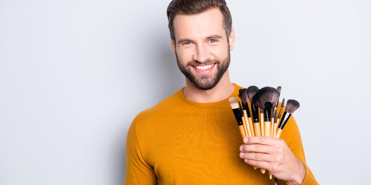 Lächelnder Mann mit Schminkpinseln in der Hand.