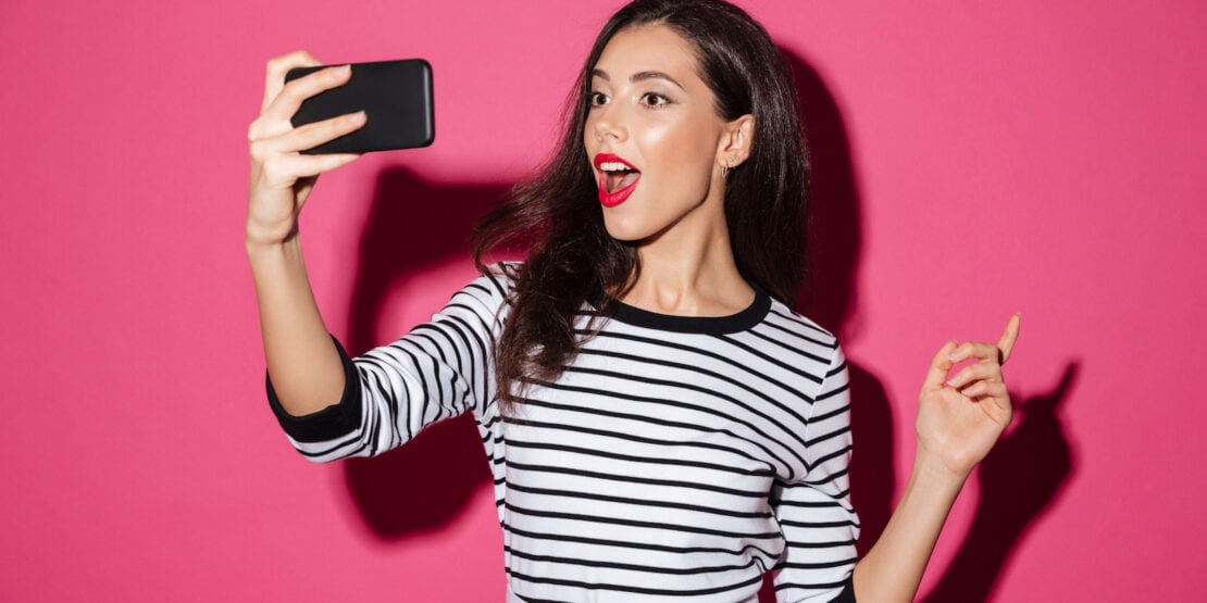 Eine junge Frau schiesst mit geöffnetem Mund ein Selfie von sich.