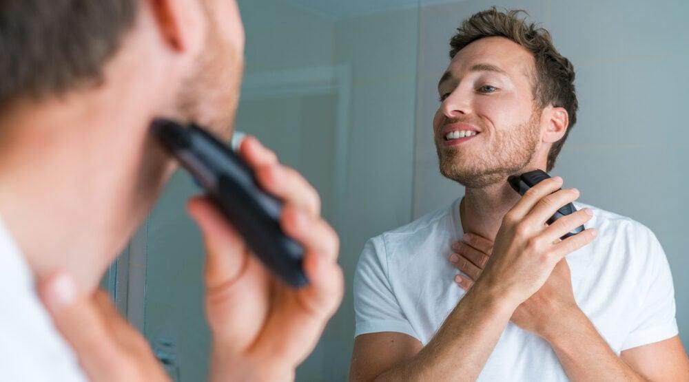 Junger Mann rasiert sich seinen Bart, damit seine Jawline maskuliner wirkt.